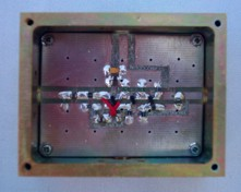 [Photograph of PCB mounted in box]