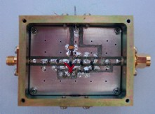 [Photograph of box with connector, feedthrough capacitor and blanking plate]